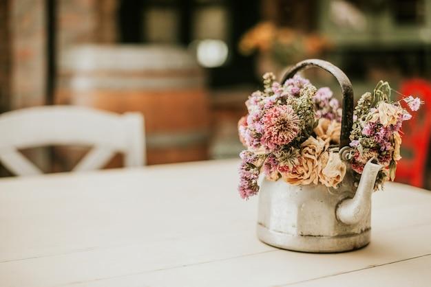 Acogedora casa de decoración rústica. flores en la tetera.