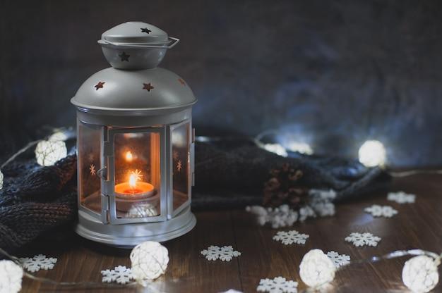 Acogedora casa de invierno. una linterna, una vela, una guirnalda, copos de nieve, un cono, un suéter de punto gris sobre una mesa de madera. la atmósfera de un cuento de hadas de año nuevo. lugar para el texto.