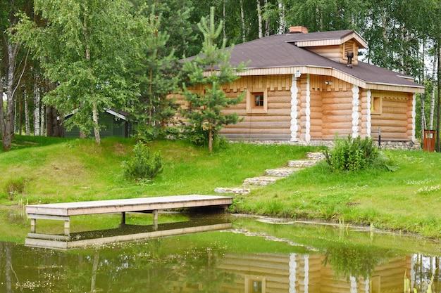 Acogedora casa de madera con un muelle en el lago