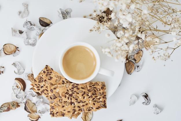 Acogedora casa con una taza de café y rama de flores.