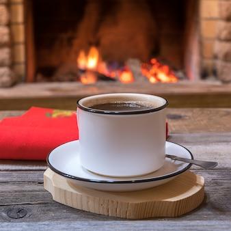 Acogedora chimenea y una taza de té, en casa de campo, vacaciones de invierno.