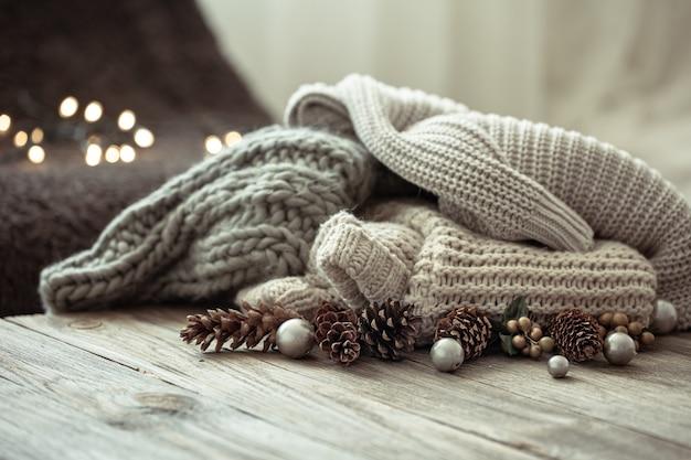 Acogedora composición navideña con una pila de suéteres de punto y conos de pino decorativos sobre un fondo borroso con bokeh.