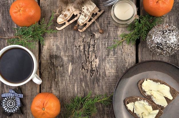 Una acogedora composición navideña de ramas de coníferas, mandarinas, una taza de café y sándwiches.