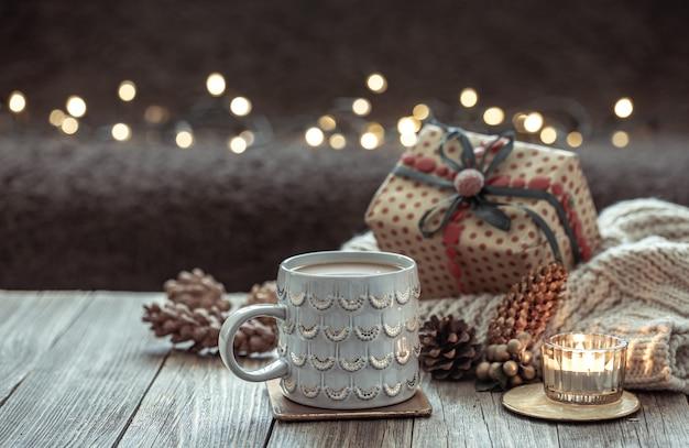 Acogedora composición navideña con una taza y detalles de decoración festiva sobre un fondo oscuro borroso con bokeh.