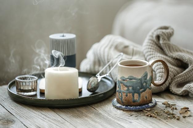 Acogedora composición con una taza de cerámica, velas y un elemento de punto sobre un fondo difuminado.