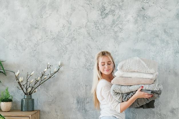 Acogedora decoración interior de dormitorio de invierno. señora con manta de punto caliente y pila de almohadas.