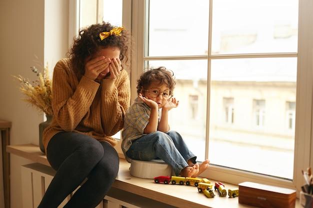 Acogedora escena de familia feliz en el interior. atractiva mujer joven con cabello rizado disfrutando de dulces momentos de maternidad, sentada en el gran alféizar de la ventana, jugando a buscar y esconderse con un adorable niño pequeño