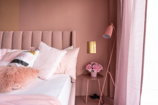 Acogedora esquina de dormitorio rosa con cama de tela de terciopelo rosa bebé decorada con una manta, almohadas y lámpara de pie rosa con pared pintada de dos tonos de rosa