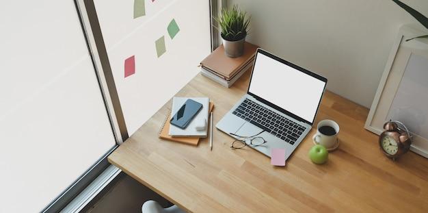 Acogedora oficina en casa con laptop abierta con pantalla en blanco