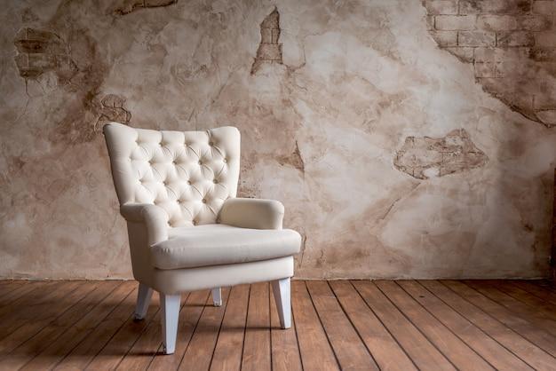 Acogedora silla grande de un tono lechoso en un interior sobre una pared de color de cacao