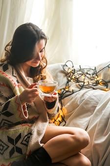 Acogedora taza de té la niña en las manos