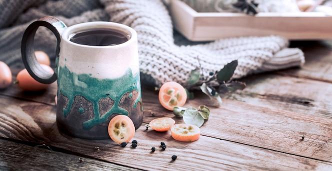 Acogedora taza de té con suéter en mesa de madera