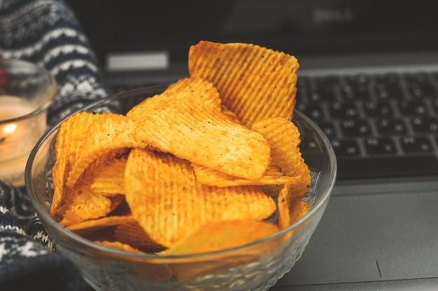 Acogedoras noches cálidas de invierno y otoño con películas y comida poco saludable, papas fritas en un tazón, suéter tejido de cerca