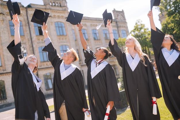 Acogiendo con beneplácito el mundo adulto. estudiantes graduados felices levantando sus gorras de maestría juntos frente a su universidad.