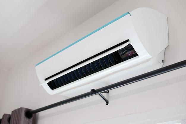 Acondicionador de aire en el fondo interior de la habitación de pared blanca
