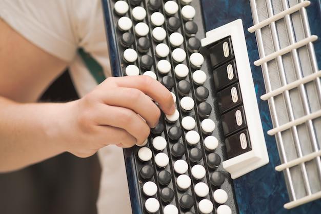 Acordeón en manos de un músico, vista de primer plano. imagen de la música callejera, músico callejero tocando un melodeón
