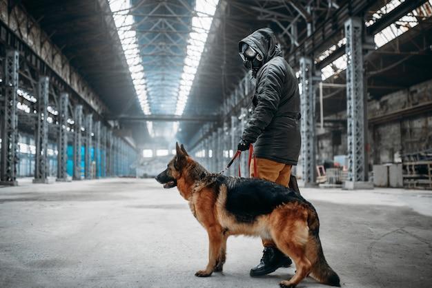 Acosador en máscara de gas y perro en edificio abandonado