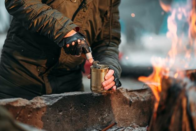 Acosador, persona del sexo masculino cocinar alimentos enlatados en llamas. estilo de vida postapocalíptico, apocalipsis