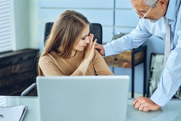 Acoso con un jefe tocando el brazo a su secretaria que está sentada en su lugar de trabajo en la oficina