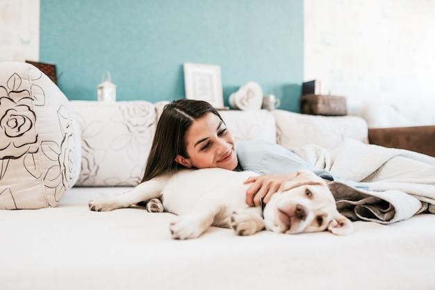 Acostado en la cama con un perro.