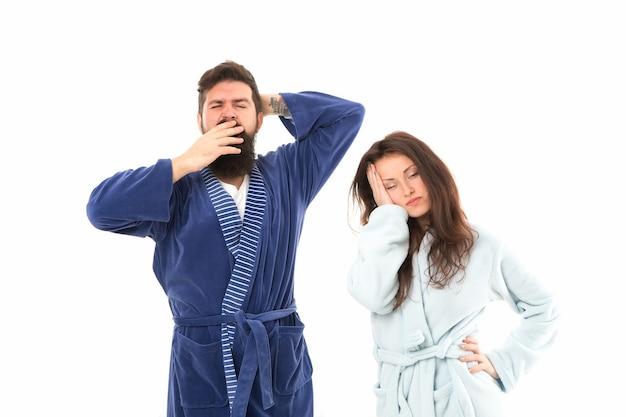 Acostarse. pijama todo el día. fondo blanco de la gente soñolienta. pareja de enamorados albornoces. somnoliento y débil por la mañana. rutina de la mañana. pareja de caras soñolientas ropa doméstica. hora de dormir. gente exhausta.