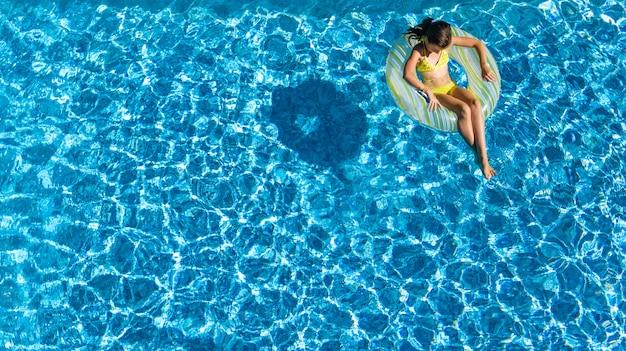 Acrive niña en la piscina vista aérea desde arriba, el niño nada en anillo inflable donut, el niño se divierte en el agua azul en el resort de vacaciones familiares