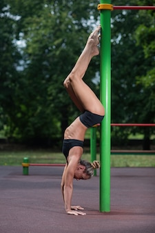 La acrobacia deportiva se levanta en sus manos y hace un elemento acrobático.
