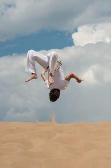 Acrobat realiza un truco acrobático, salto mortal en la playa.