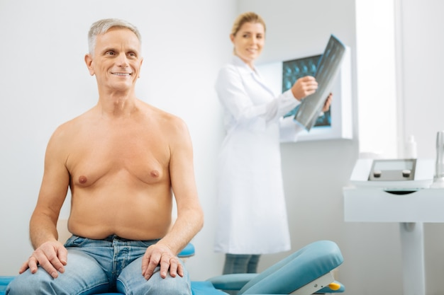 Actitud optimista. hombre mayor encantado alegre que se sienta en la cama médica y que sonríe mientras está en el estado de ánimo positivo