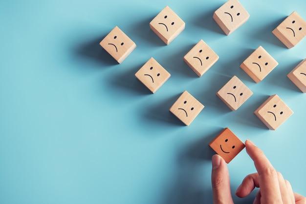 Actitud positiva y concepto feliz. mano elija cubo de madera una cara sonriente rodeada emoción triste sobre fondo azul.