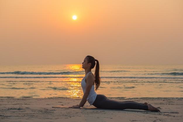 Actitud practicante de la yoga de la mujer sana joven de la yoga en la playa en la salida del sol