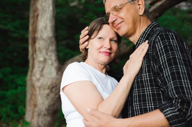 Activa pareja amorosa senior caminando en el hermoso bosque de verano