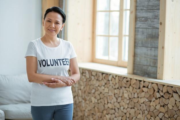 Actividad altruista. voluntaria inteligente satisfecha de pie mientras mira a la cámara y sonríe