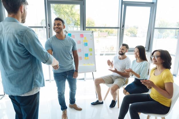 Actividad de teambuilding. hombres positivos guapos alegres que se miran y se dan la mano mientras hacen una actividad de trabajo en equipo