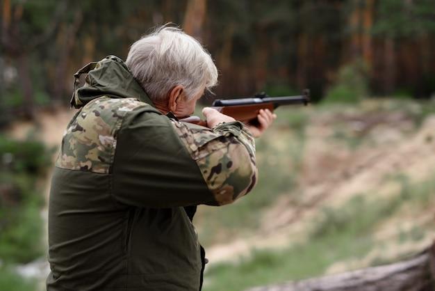 Actividades de verano abuelo caza en el bosque.