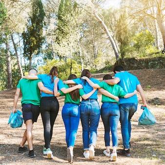 Activistas abrazándose caminando con bolsas de basura en el bosque
