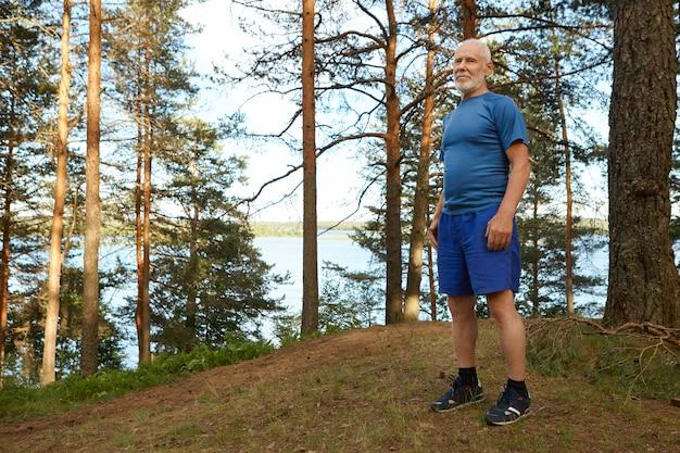 Activo guapo maduro sizty año viejo vistiendo elegante ropa deportiva de pie sobre la hierba seca en el bosque contra los árboles y el vasto lago. concepto de energía, naturaleza, envejecimiento y jubilación