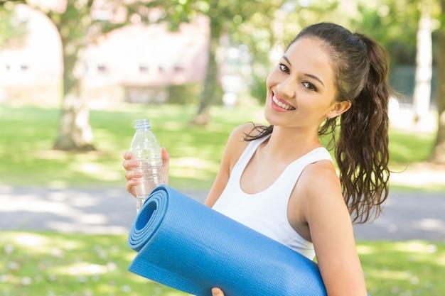 Activo sonriente morena con colchoneta de ejercicios