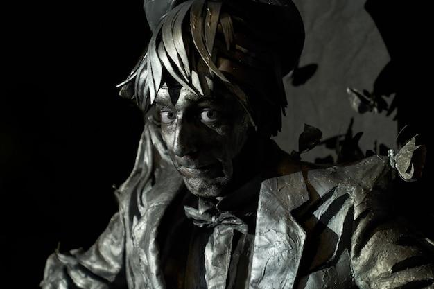 Actor cómico como una pantomima con maquillaje facial de bronce y en traje pintado parado como una estatua sobre fondo negro. artista mimo mostrando su profesionalismo en la actuación dramática.