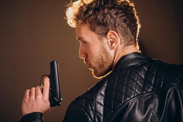 Actor guapo posando en estudio con arma