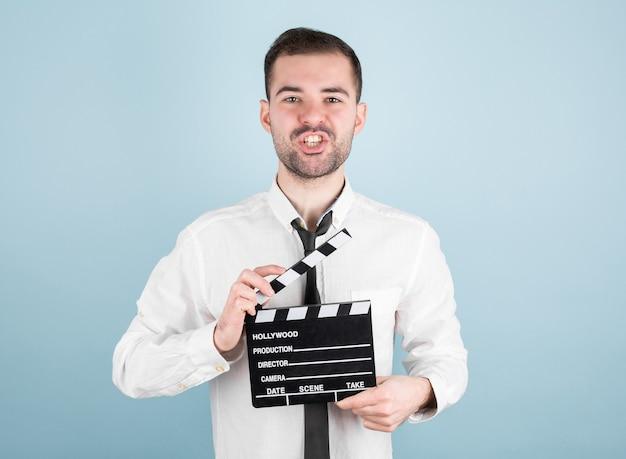 Actor masculino profesional listo para filmar la película, sostiene el badajo de la película, aislado en la pared azul.