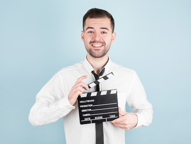 Actor masculino profesional listo para filmar películas, sostiene badajo de película, en azul.