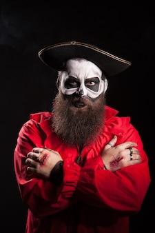 Actor con sangre en sus manos vistiendo un traje de pirata espeluznante.