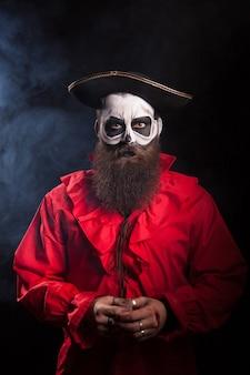 Actor vistiendo un disfraz de pirata para halloween sobre fondo negro.