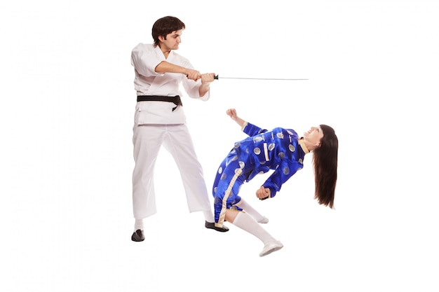 Los actores en un kimono pelean con un sable entre sí aislado sobre el fondo blanco.
