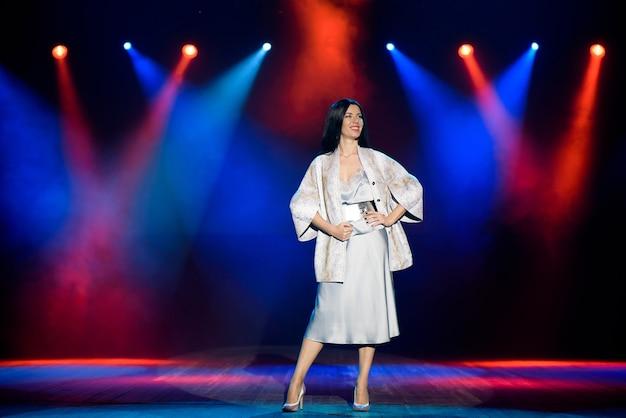 Actriz en el escenario en coloridos rayos de luz brillante