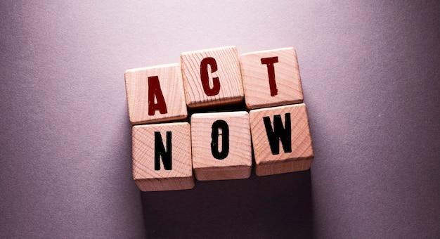 Actuar ahora palabra escrita en cubos de madera