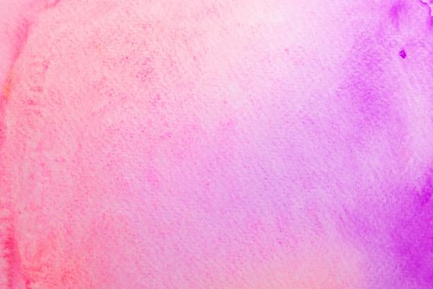 Acuarela abstracta de color rosa y violeta sobre papel.
