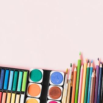 Acuarela y pinceles cerca de herramientas de dibujo