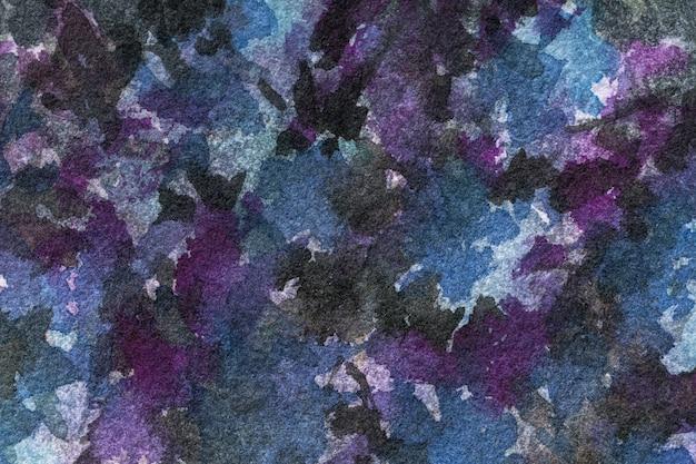 Acuarela sobre lienzo con manchas negras, azules y moradas.
